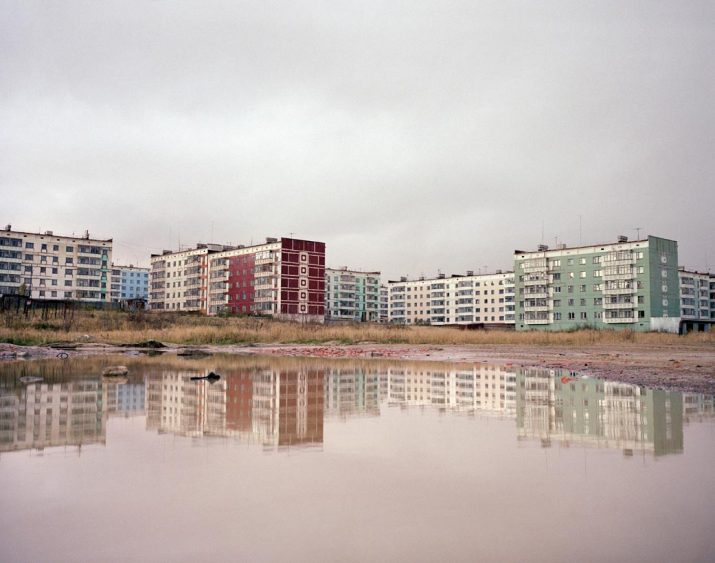 Apartment blocks reflected in water, Sakhalin Island, Far East Russia, October 2004